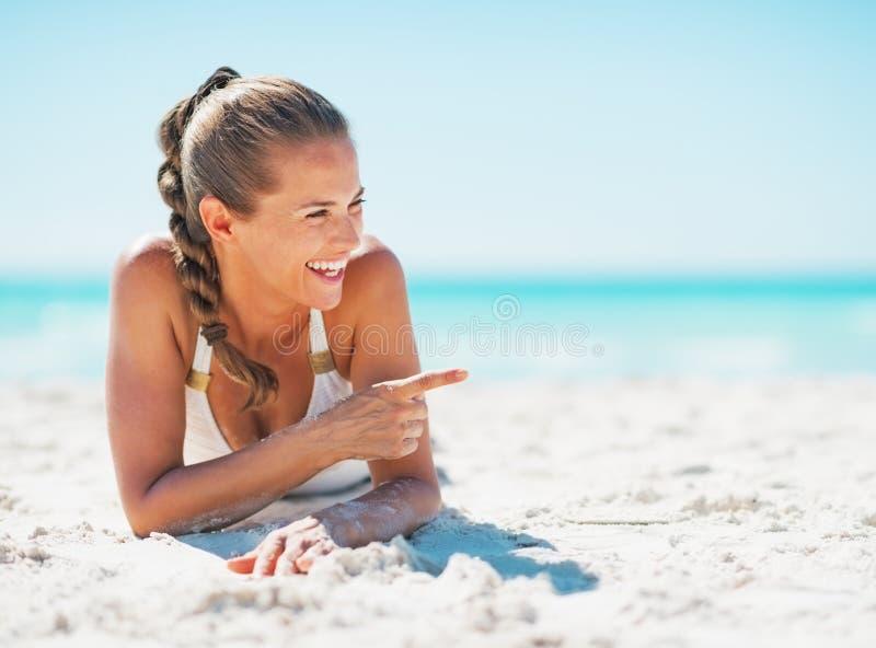 Mujer sonriente que pone en la playa y que señala en espacio de la copia foto de archivo libre de regalías