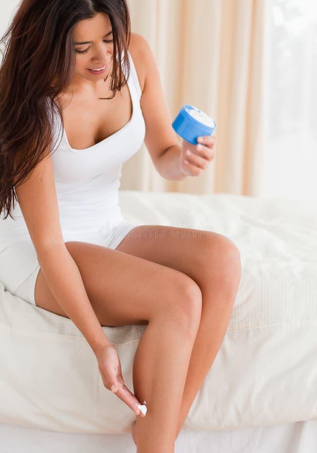 Mujer sonriente que pone la nata en sus piernas imagenes de archivo