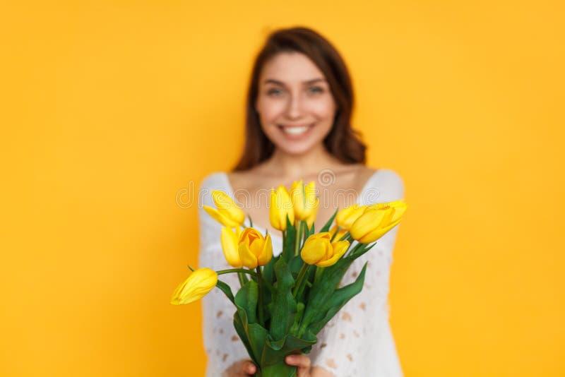 Mujer sonriente que presenta con los tulipanes imagen de archivo