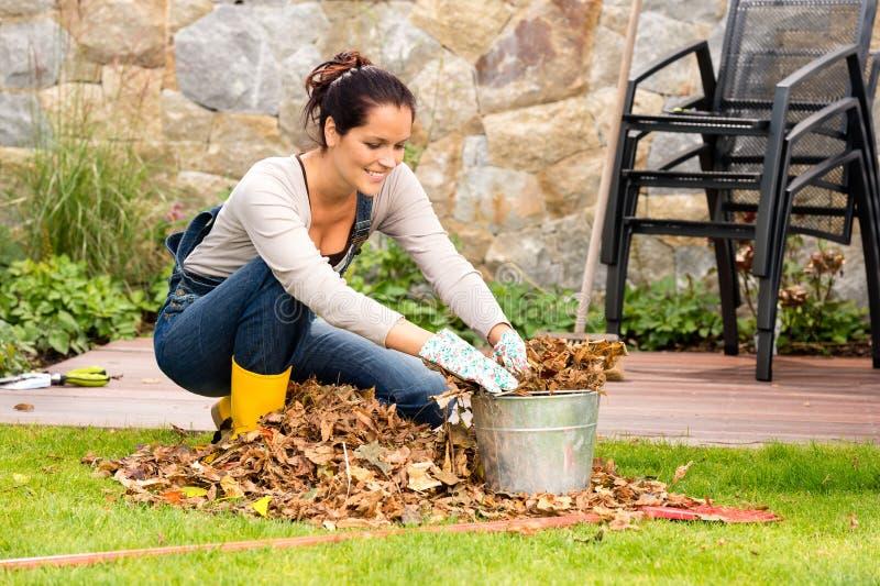 Mujer sonriente que rellena cultivar un huerto del otoño del cubo de las hojas imagenes de archivo