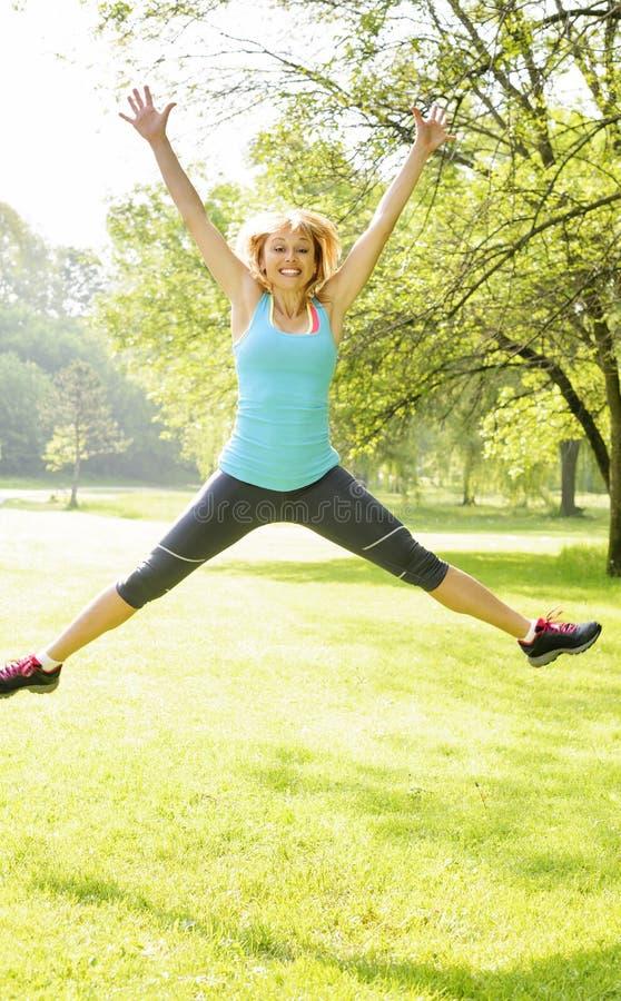 Mujer sonriente que salta en parque fotografía de archivo