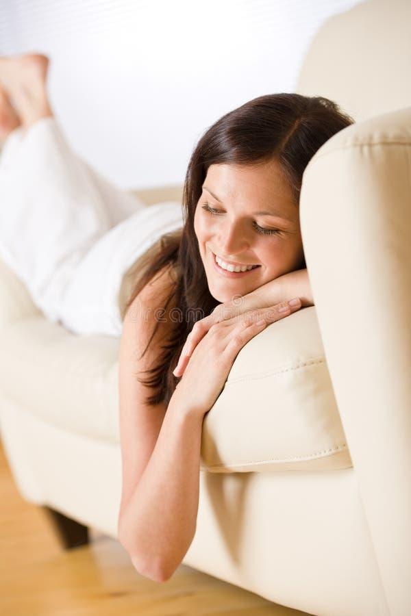 Mujer sonriente que se acuesta en el sofá fotografía de archivo