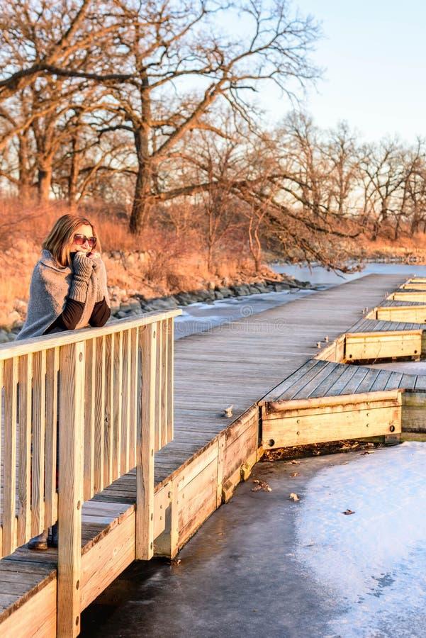 Mujer sonriente que se coloca en el puente de madera en invierno fotos de archivo libres de regalías