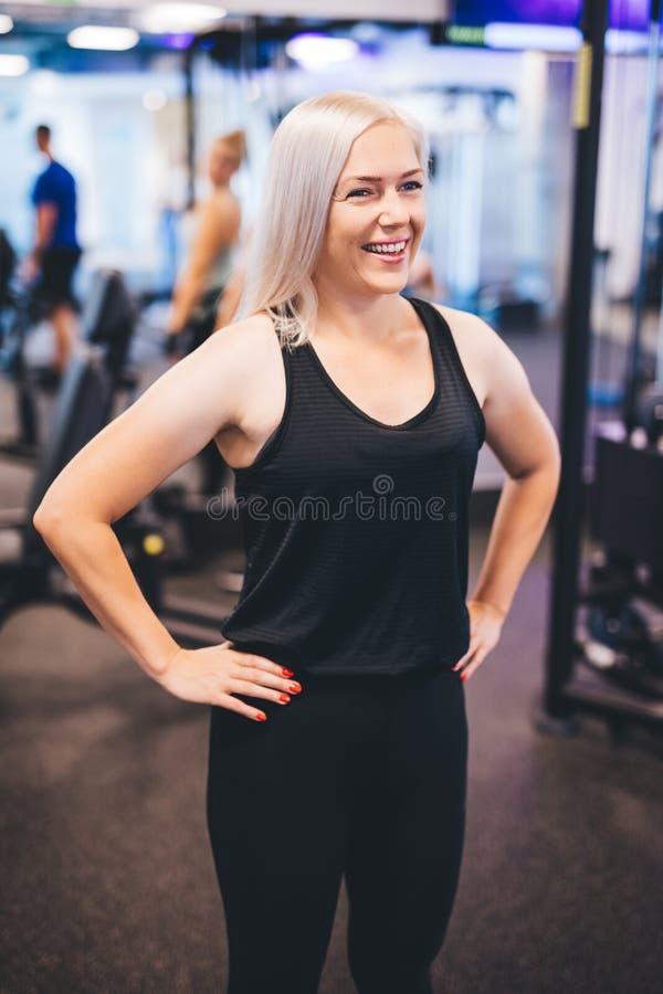 Mujer sonriente que se coloca en un gimnasio imagen de archivo