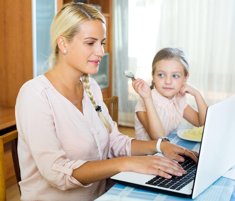 Mujer sonriente que se sienta con el ordenador portátil en casa foto de archivo libre de regalías