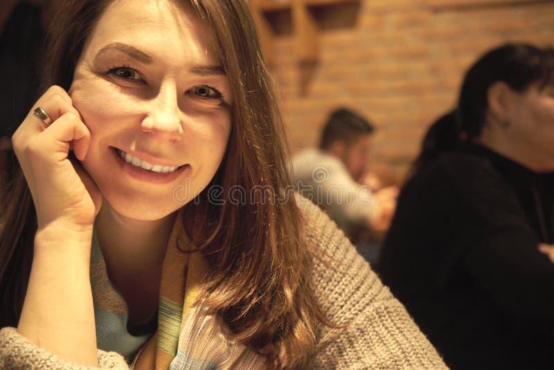 Mujer sonriente que se sienta dentro imagenes de archivo