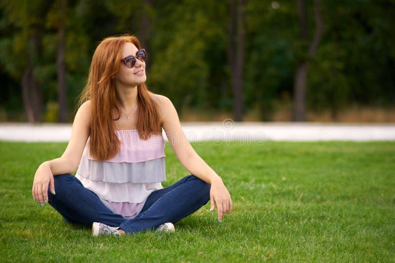 Mujer sonriente que se sienta en el césped verde fotografía de archivo libre de regalías