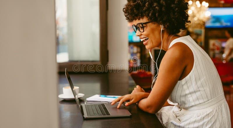 Mujer sonriente que se sienta en el café usando el ordenador portátil foto de archivo libre de regalías