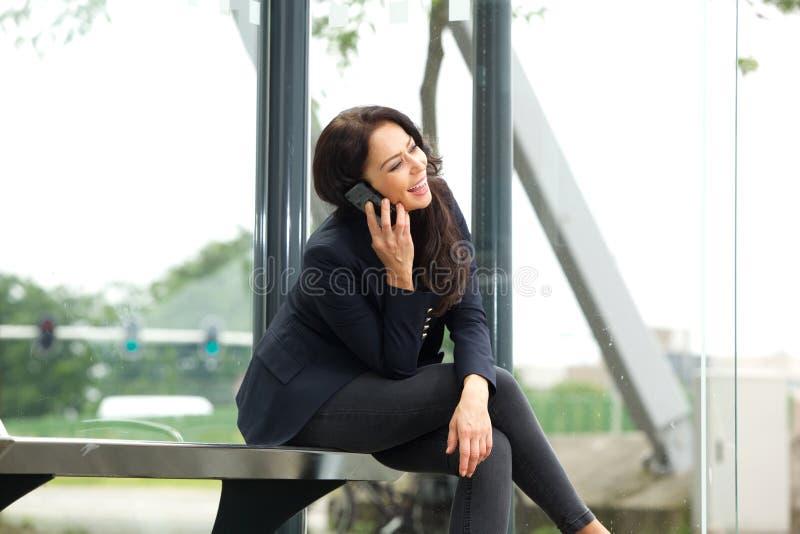 Mujer sonriente que se sienta en la parada de autobús que habla en el teléfono móvil imagen de archivo libre de regalías