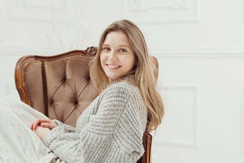 Mujer sonriente que se sienta en la silla del vintage, rodillas cubiertas por la manta fotografía de archivo libre de regalías