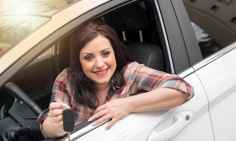 Mujer sonriente que se sienta en nuevo coche y mostrar las llaves del coche, efecto luminoso foto de archivo libre de regalías