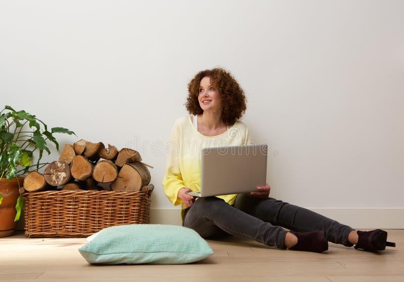 Mujer sonriente que se sienta en piso con el ordenador portátil en casa foto de archivo libre de regalías