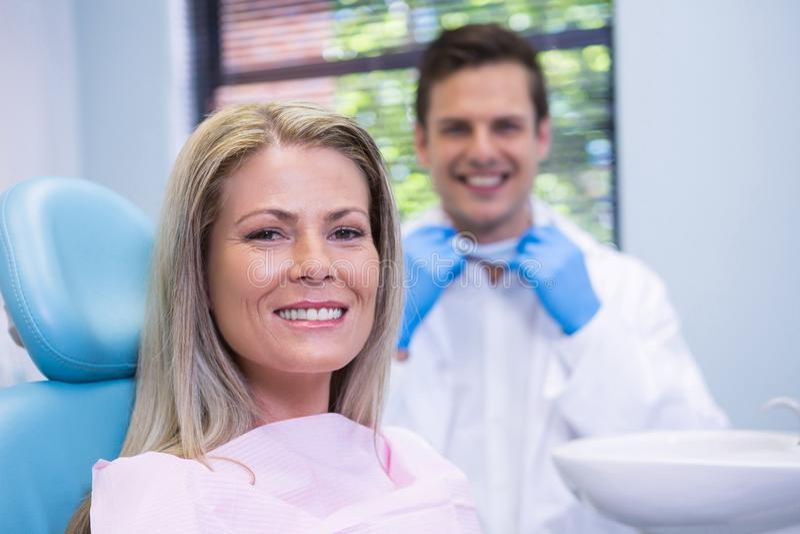 Mujer sonriente que se sienta en silla contra dentista en la clínica médica fotos de archivo libres de regalías