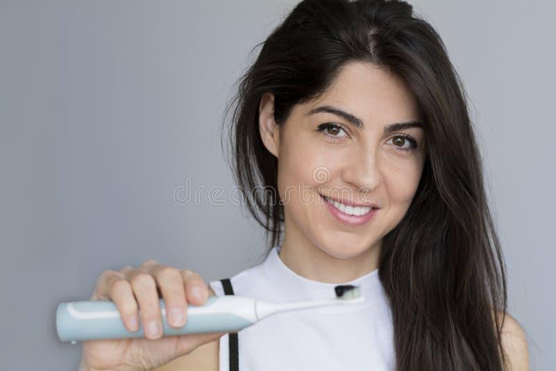 Mujer sonriente que sostiene el cepillo de dientes con crema dental negra del carbón de leña foto de archivo