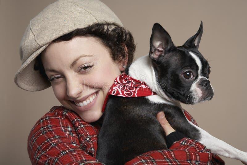 Mujer sonriente que sostiene el dogo francés imagen de archivo