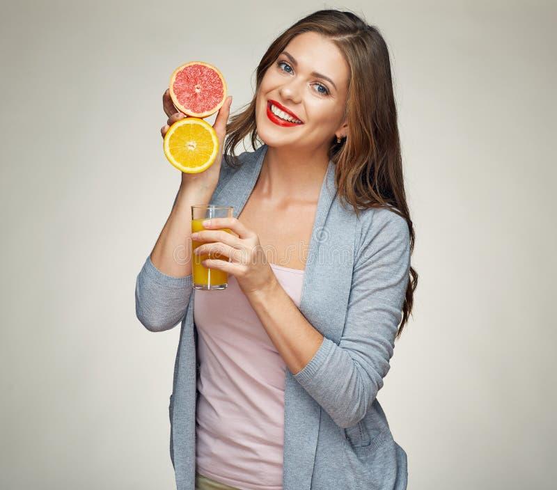 Mujer sonriente que sostiene el jugo de cristal con a medias anaranjado y grapefrui imagenes de archivo