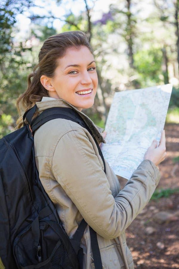 Mujer sonriente que sostiene el mapa foto de archivo