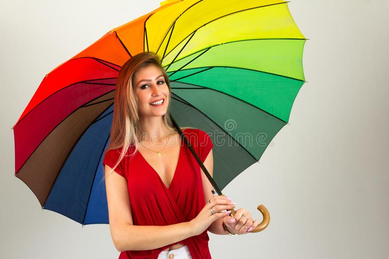 Mujer sonriente que sostiene el paraguas colorido Persona y weari rubios imágenes de archivo libres de regalías