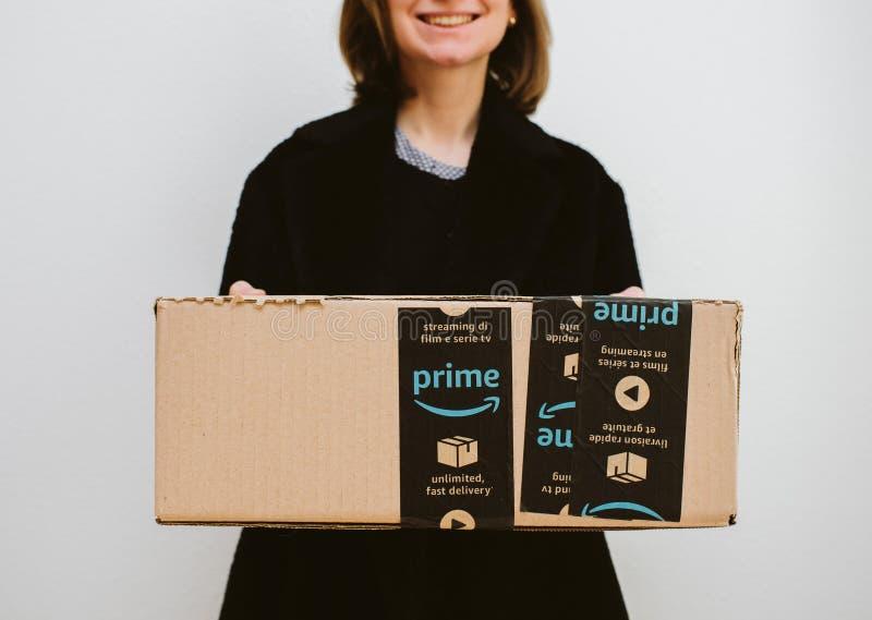 Mujer sonriente que sostiene la caja de cartón primera del paquete del Amazonas imagenes de archivo