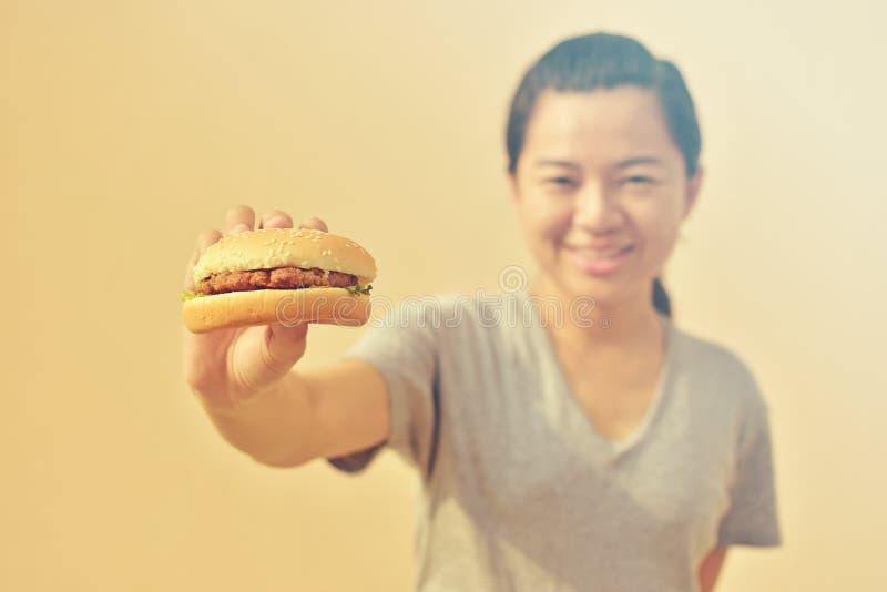 Mujer sonriente que sostiene la hamburguesa comida malsana disponible, americana imagen de archivo libre de regalías