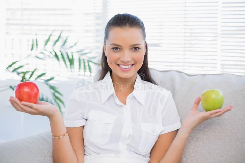 Mujer sonriente que sostiene la manzana roja y verde que se sienta en el sofá fotografía de archivo libre de regalías