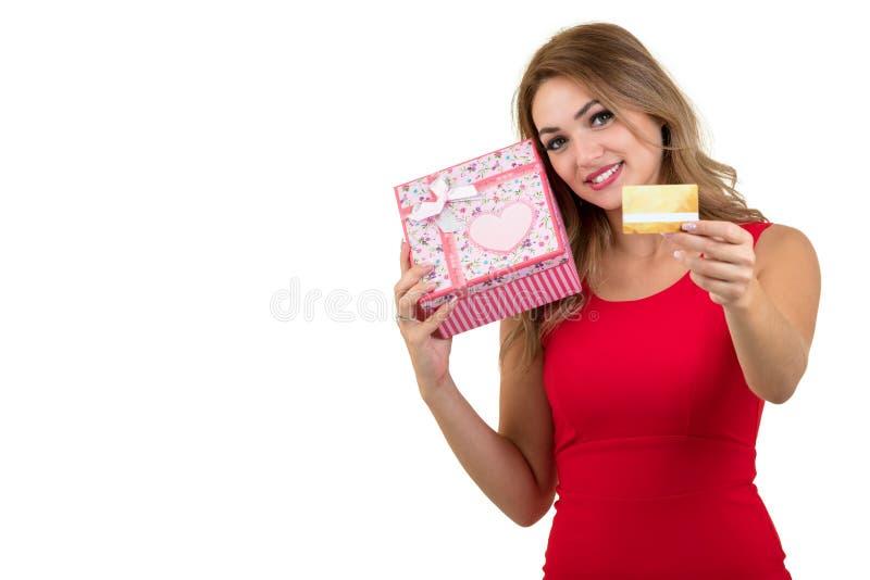 Mujer sonriente que sostiene la tarjeta de banco y caja de regalo aislada en un fondo blanco imagen de archivo libre de regalías
