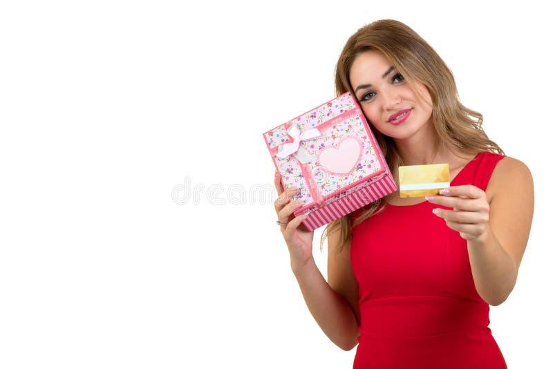 Mujer sonriente que sostiene la tarjeta de banco y caja de regalo aislada en un fondo blanco fotografía de archivo
