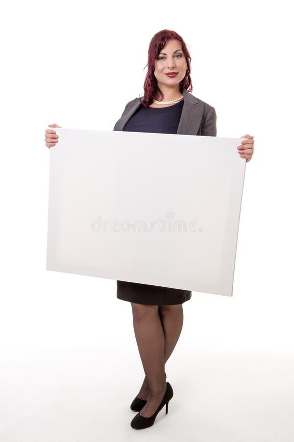 Mujer sonriente que sostiene la tarjeta en blanco fotos de archivo