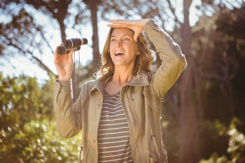 Mujer sonriente que sostiene los prismáticos imágenes de archivo libres de regalías