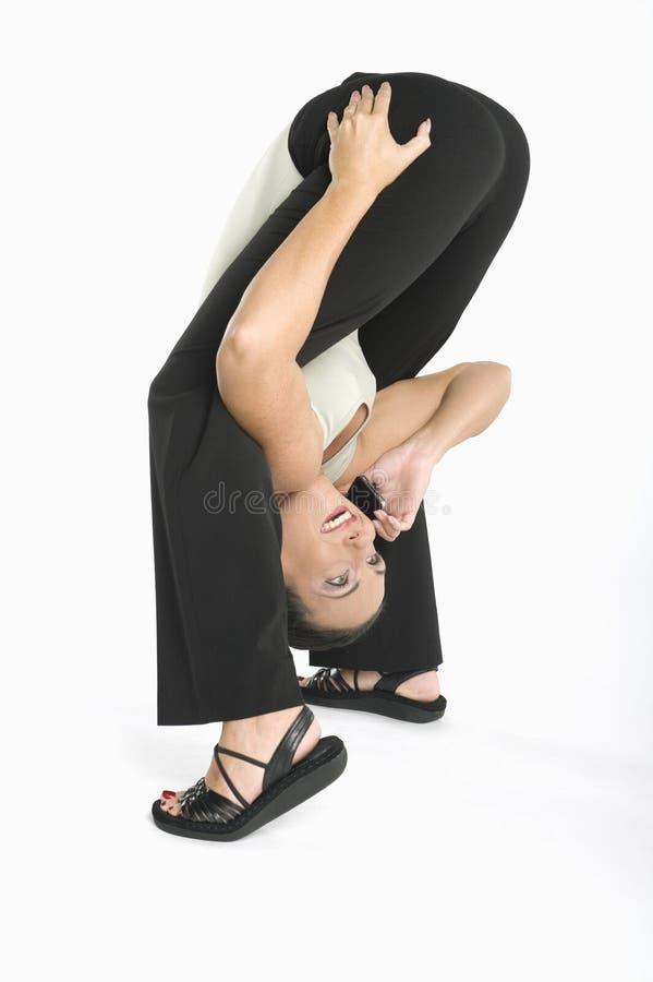 Mujer sonriente que tiene conversación sobre el teléfono celular mientras que ejercita fotos de archivo