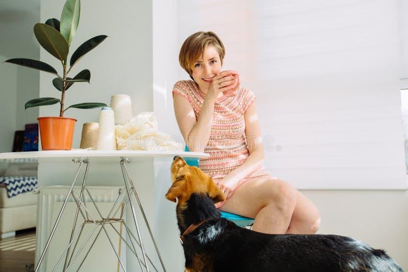 Mujer sonriente que tiene rotura con la taza de café en el lugar de trabajo acogedor en casa interior En cámara de mirada femenin imagenes de archivo