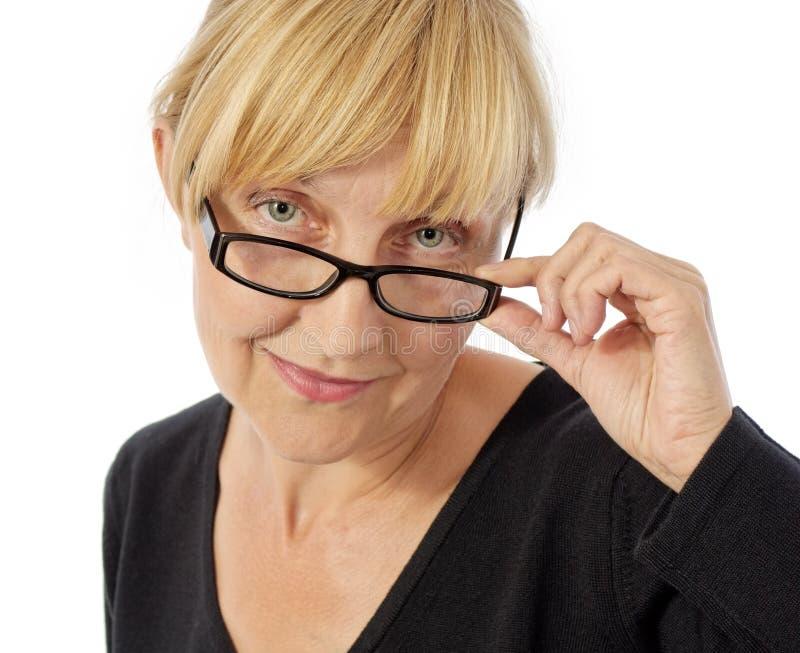 Mujer sonriente que toca sus vidrios imagen de archivo libre de regalías