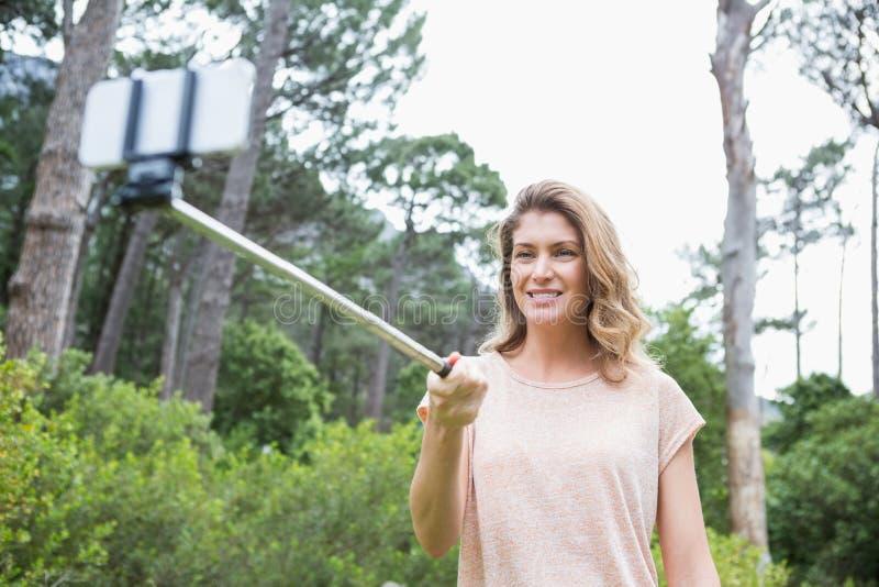 Mujer sonriente que toma selfies foto de archivo