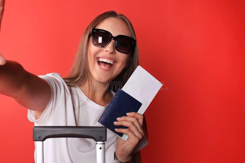 Mujer sonriente que toma un selfie con las gafas de sol mientras que sostiene el pasaporte con la maleta roja, aislada en fondo r fotografía de archivo