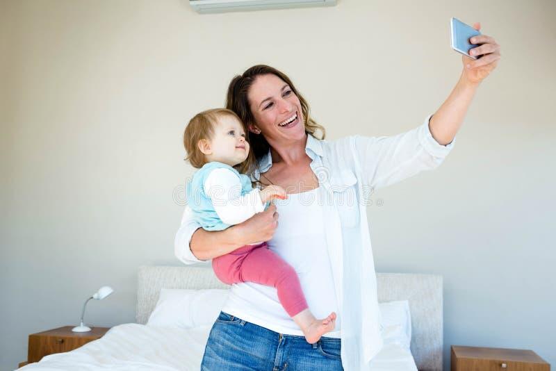 Mujer sonriente que toma un selfie con su bebé imagen de archivo