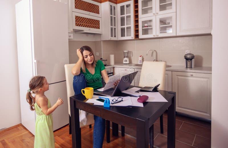 Mujer sonriente que trabaja de hogar con el ordenador mientras que mira el afte fotos de archivo libres de regalías