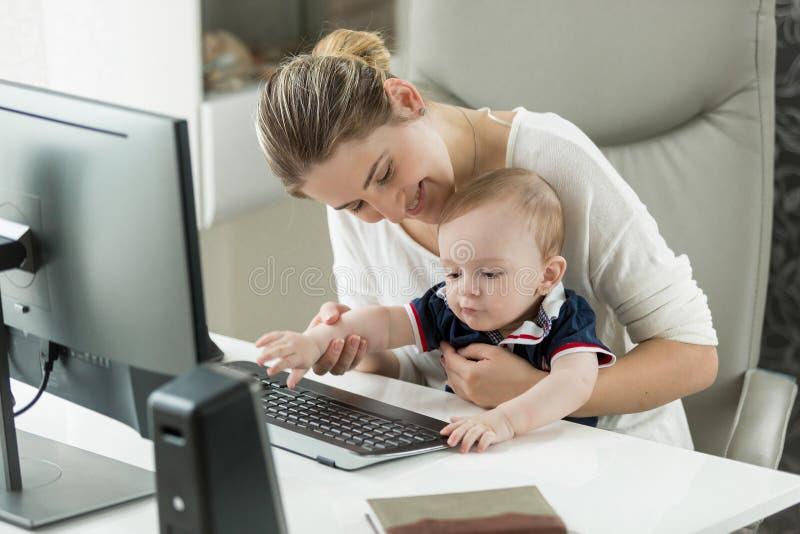 Mujer sonriente que trabaja en casa y detener a su hijo del bebé en revestimiento foto de archivo