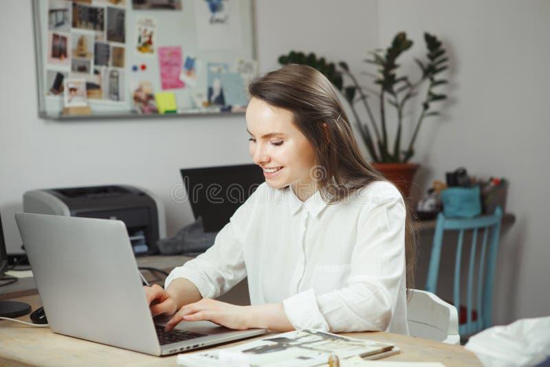 Mujer sonriente que trabaja en el ordenador, empresaria feliz fotos de archivo libres de regalías