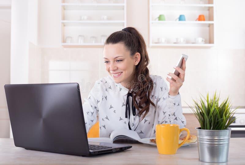 Mujer sonriente que trabaja en el ordenador portátil en cocina foto de archivo libre de regalías