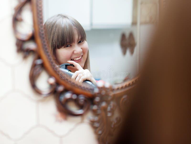 Mujer sonriente que usa el hierro que se encrespa fotos de archivo libres de regalías