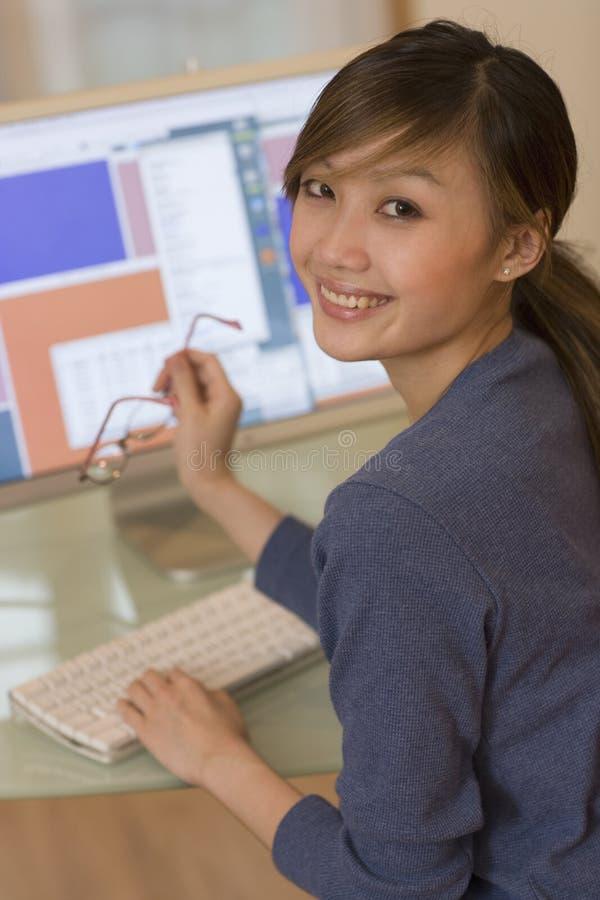 Mujer sonriente que usa el ordenador imagen de archivo libre de regalías