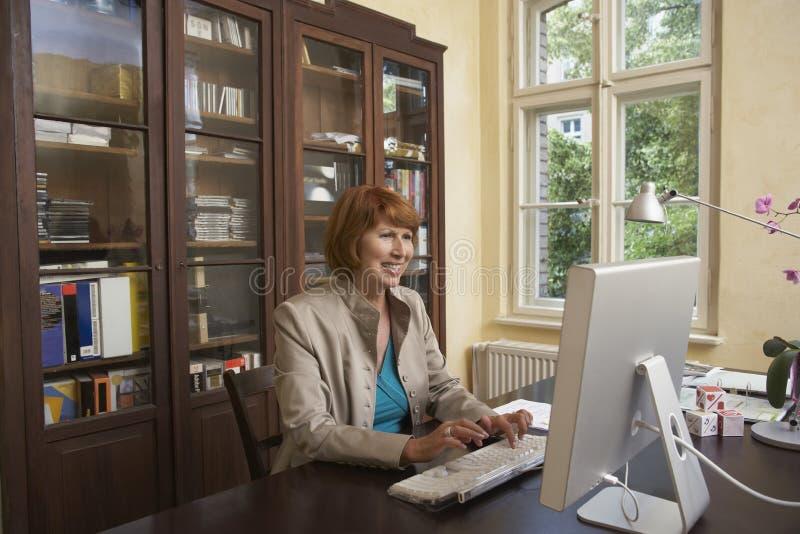 Mujer sonriente que usa el ordenador en sitio de estudio imagen de archivo