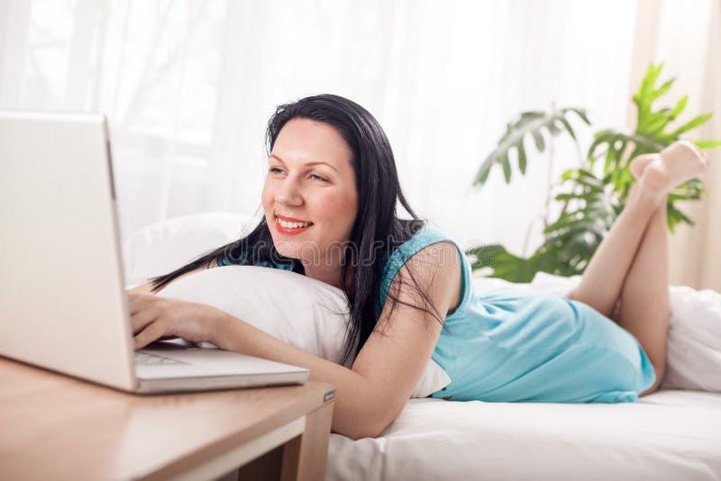 Mujer sonriente que usa el ordenador portátil en casa en dormitorio fotografía de archivo
