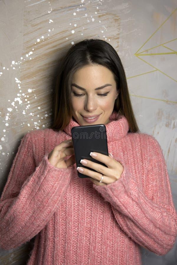 Mujer sonriente que usa el teléfono celular foto de archivo libre de regalías