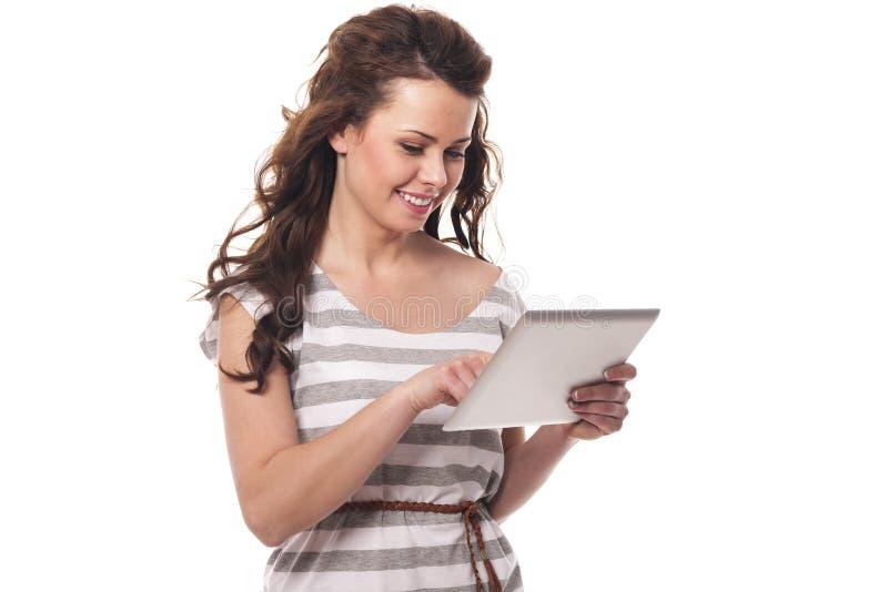 Mujer sonriente que usa la tableta fotografía de archivo libre de regalías