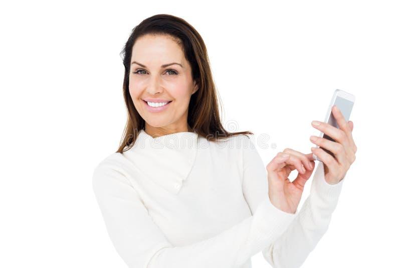 Mujer sonriente que usa smartphone foto de archivo libre de regalías