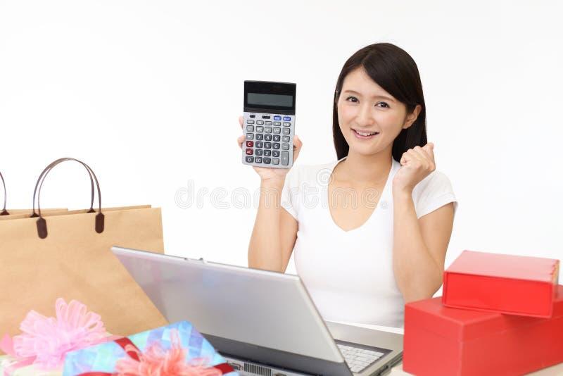 Mujer sonriente que usa una computadora portátil fotografía de archivo