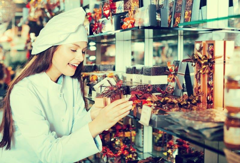 Mujer sonriente que vende los regalos de chocolates finos imágenes de archivo libres de regalías