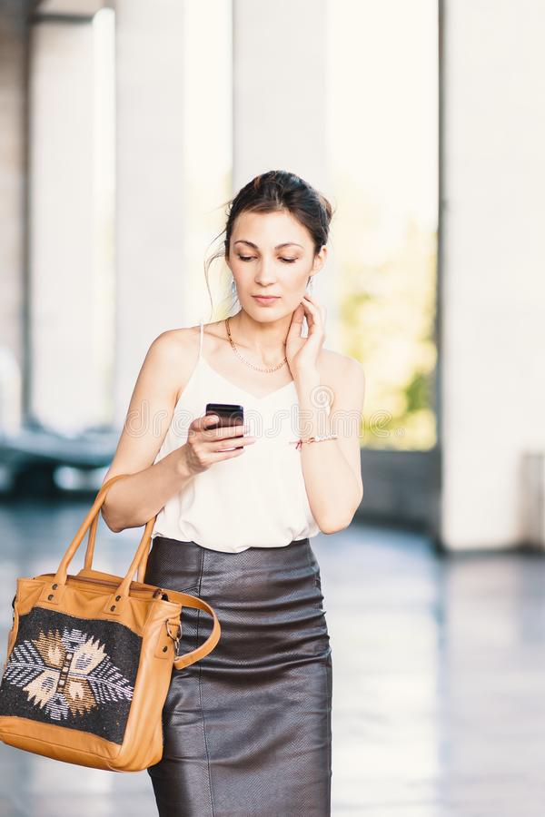Mujer sonriente refinada que camina y que escribe o que lee los mensajes de SMS en línea en outdors elegantes de un teléfono foto de archivo libre de regalías