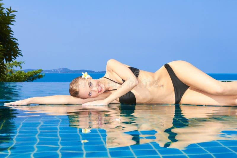 Mujer sonriente reflejada en piscina foto de archivo libre de regalías